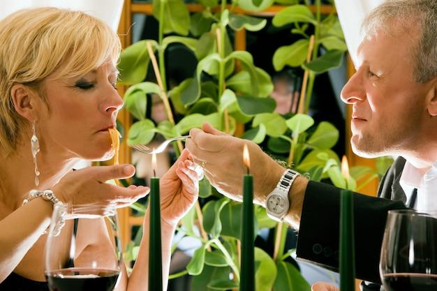 Reife paare, die romantisches abendessen in einem fantastischen restaurant essen
