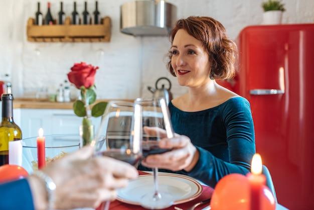 Reife paare, die zu hause romantisch für valentinstag zu abend essen und toast mit rotwein tun