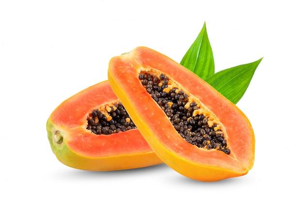 Reife papaya-scheibe mit blättern auf weißer wand.