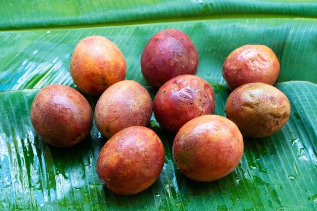 Reife passionsfrucht auf einem feuchten bananenblatt. vitamine, obst, gesunde lebensmittel