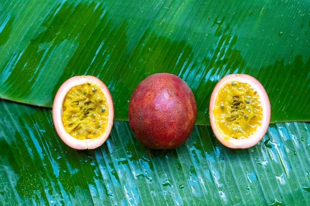Reife passionsfrucht auf nassem bananenblatt. vitamine, obst, gesunde lebensmittel