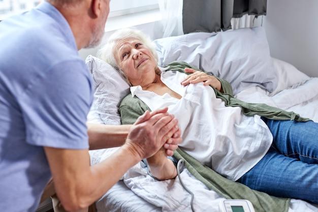 Reife patientin im krankenhaus mit besorgtem ehemann, der hände hält, während blutdruck mit tonometer prüft. mann hilft, unterstützt