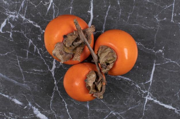 Reife persimonenfrüchte auf marmor.