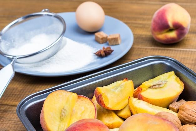 Reife pfirsiche in metallschale. mehl, sieb und ei auf grauem teller. hölzerner hintergrund. ansicht von oben