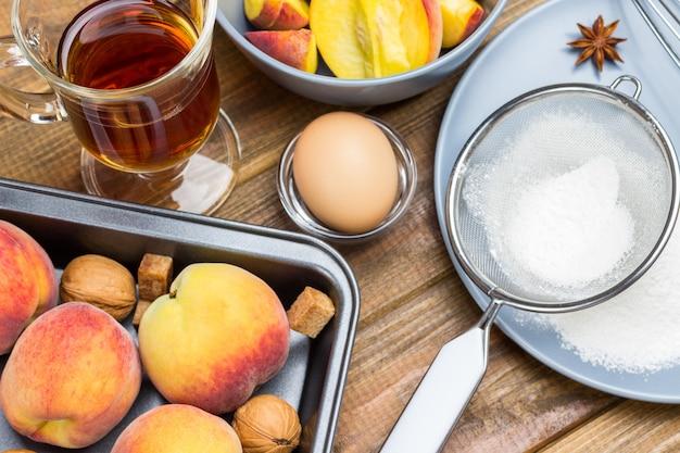 Reife pfirsiche in metallschale. mehl und sieb auf grauem teller. glas tee und geschnittene äpfel in grauer platte. hölzerner hintergrund. ansicht von oben