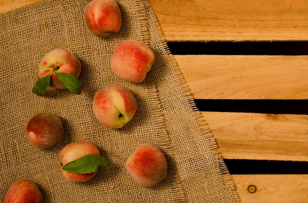 Reife pfirsiche mit blättern auf sackleinen und holzplatten