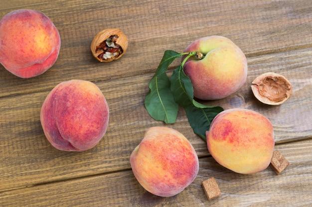 Reife pfirsiche mit grünen blättern auf dem tisch. hölzerner hintergrund. ansicht von oben