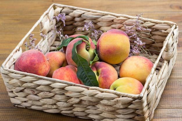 Reife pfirsiche mit grünen blättern im weidenkorb. hölzerner hintergrund. ansicht von oben