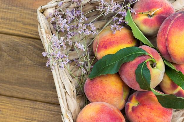 Reife pfirsiche mit grünen blättern im weidenkorb. hölzerner hintergrund. flach legen