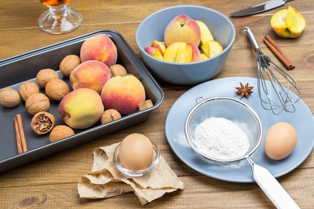 Reife pfirsiche und walnüsse im metalltablett. mehl, sieb und ei auf grauem teller. geschnittene pfirsiche in grauer platte. hölzerner hintergrund. ansicht von oben