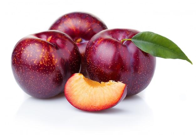 Reife purpurrote pflaume trägt mit den grünen blättern früchte, die auf weiß lokalisiert werden