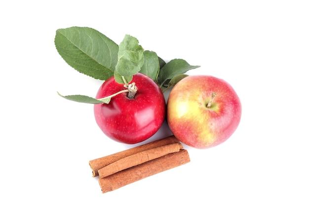 Reife rote äpfel mit blättern und zimtstangen auf weißem, isoliertem hintergrund