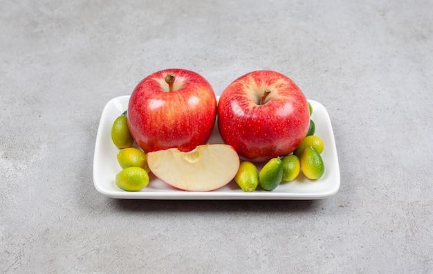 Reife rote äpfel mit haufen kumquats