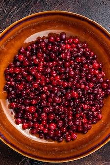 Reife rote cranberry-beere in einem rustikalen teller. dunkler hintergrund. ansicht von oben.