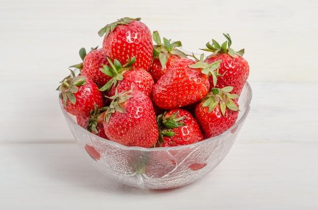 Reife rote erdbeeren in einer schüssel auf einem weißen holztisch, seitenansicht