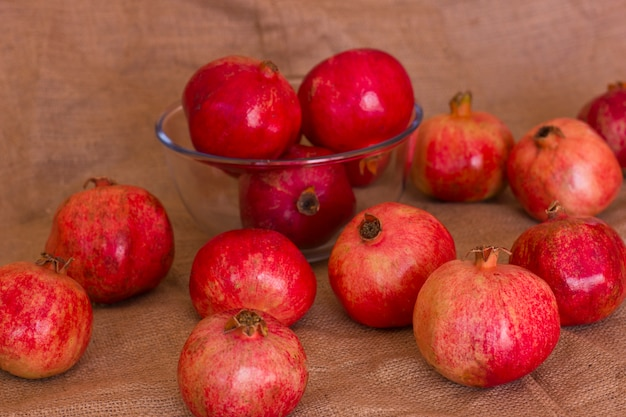 Reife rote granatäpfel in einer glasschüssel auf einer braunen leinwand