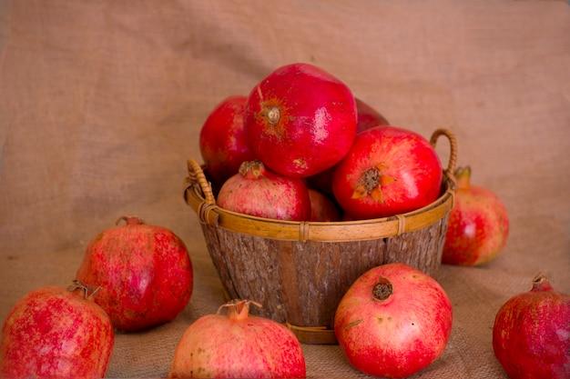 Reife rote granatäpfel in einer hölzernen schüssel auf einer braunen leinwand