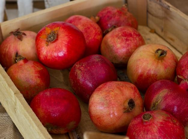 Reife rote granatäpfel in einer holzkiste auf brauner leinwand