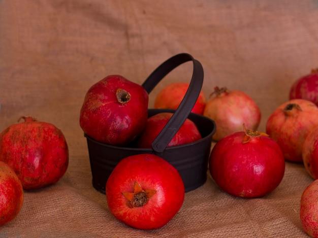 Reife rote granatäpfel in einer metallschwarzschüssel auf einer braunen leinwand