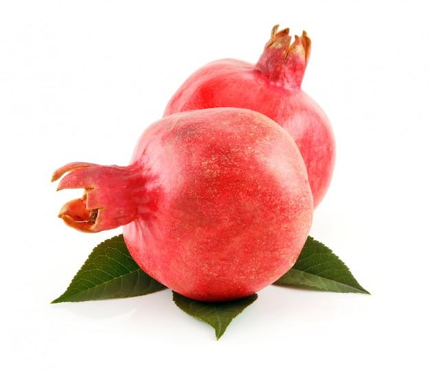 Reife rote granatapfel-früchte mit den blättern lokalisiert