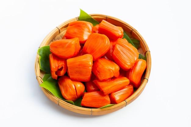 Reife rote jackfrucht auf bananenblättern im hölzernen bambusdreschkorb.