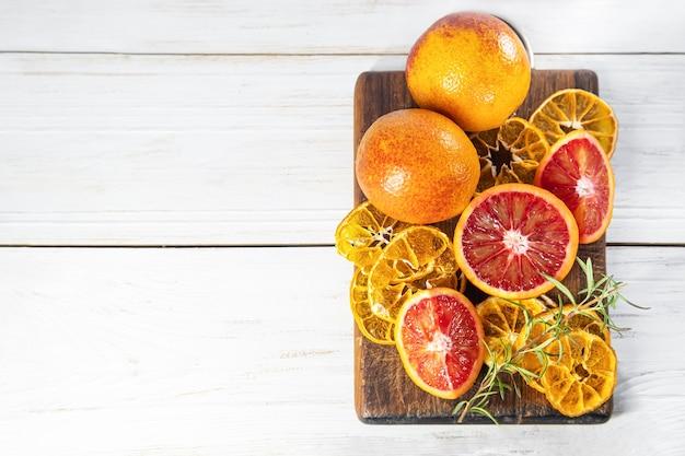 Reife rote orangen auf holzbrett. geschnittene reife saftige sizilianische blutorangen auf hölzernem hintergrund. platz kopieren.