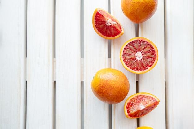 Reife rote orangen auf holzuntergrund. geschnittene reife saftige sizilianische blutorangen auf weißem hintergrund aus holz. platz kopieren.