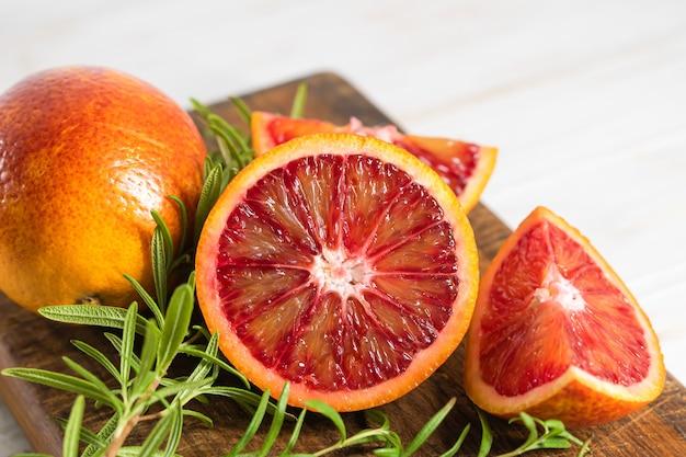 Reife rote orangen auf holzuntergrund. geschnittene reife saftige sizilianische blutorangen auf weißem hintergrund aus holz.