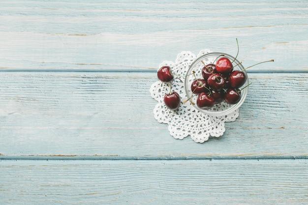 Reife rote süße kirschen auf blauem hölzernem hintergrund. flacher laienstil. buntes konzept der diät und des gesunden lebensmittels.