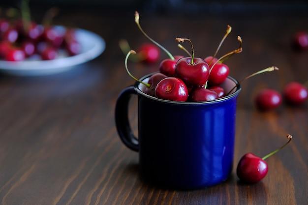 Reife rote süßkirsche in einem glas. saftige beeren und früchte. vegetarismus, veganismus, rohkost. richtige gesunde ernährung