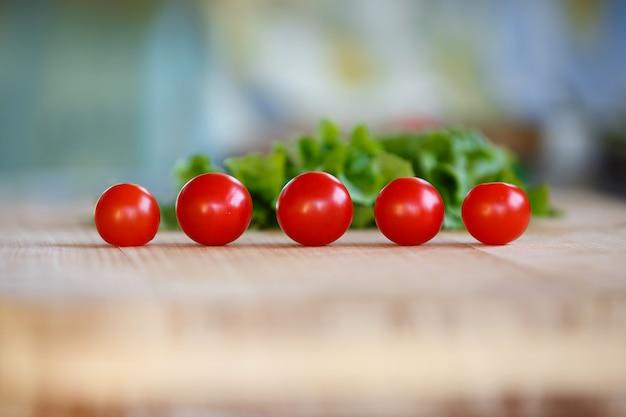 Reife rote tomaten auf einer tabelle gegen grüne blätter des kopfsalates.