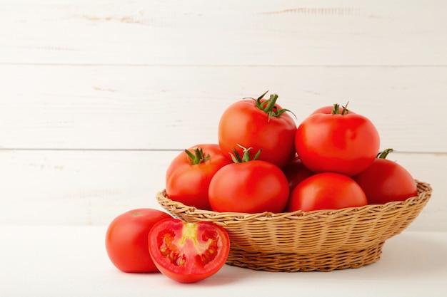 Reife rote tomaten im korb auf weißem hintergrund.
