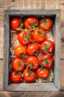 Reife rote tomaten in der hölzernen marktkiste. holzhintergrund. draufsicht.