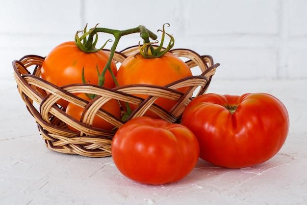 Reife rote und gelbe tomaten der nahaufnahme und ein weidenkorb auf dem weißen strukturierten hintergrund. zutaten für vegetarisches essen.