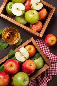 Reife rote und grüne äpfel in holzkiste mit glas frischem saft auf rostigem hintergrund. ansicht von oben.