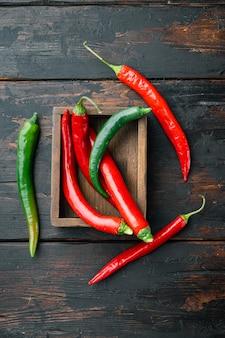 Reife rote und grüne chili-pfeffer-set, in holzkiste, auf dunklem holzhintergrund, draufsicht flach legen