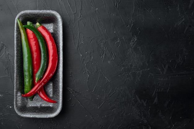 Reife rote und grüne chili-pfeffer-set, in plastikschale, auf schwarzem hintergrund, draufsicht flach, mit copyspace und platz für text