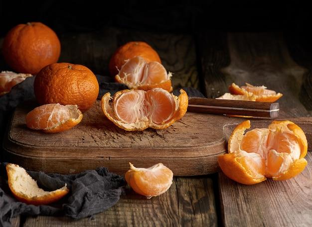 Reife runde mandarinen und schnitt zur hälfte auf einem alten weinleseschneidebrett
