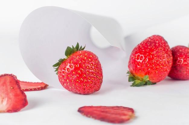 Reife saftige erdbeere mit getrockneten chips auf abstrakten weißen hintergrund verstreut. fruchtchips. gesundes ernährungskonzept, snack, kein zucker. ansicht von oben, kopienraum.