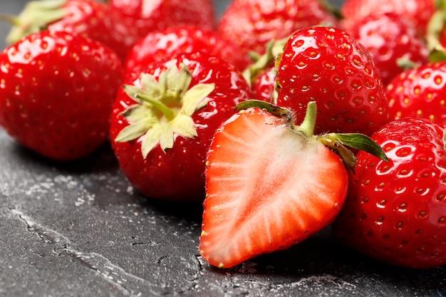 Reife saftige erdbeeren auf dunklem hintergrund nahaufnahme. ansicht von oben