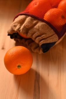 Reife saftige orange zerbröckelte aus einer segeltuchtasche auf einer holzoberfläche heraus