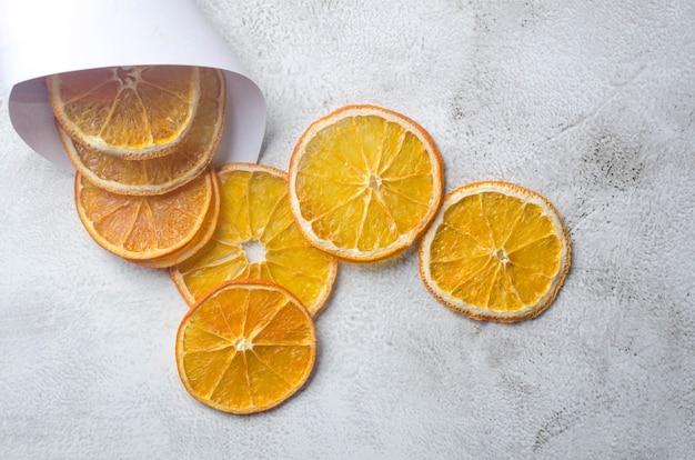 Reife saftige orangen auf grauem hintergrund und getrocknete orangenchips herum. fruchtchips. gesundes ernährungskonzept, snack, kein zucker. ansicht von oben, kopienraum.