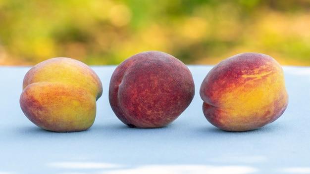 Reife saftige pfirsiche auf dem tisch im garten bei sonnigem wetter