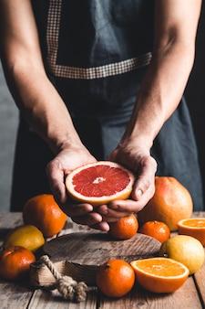 Reife saftige süße orange mandarinen in einer menschlichen hand vor einem dunklen hintergrund.