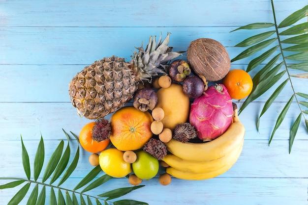 Reife saftige tropische früchte und palmblätter auf blauer holzoberfläche