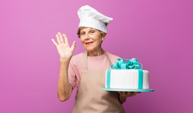 Reife schöne alte frau, die glücklich und fröhlich lächelt, hand winkt, sie begrüßt und begrüßt oder sich verabschiedet