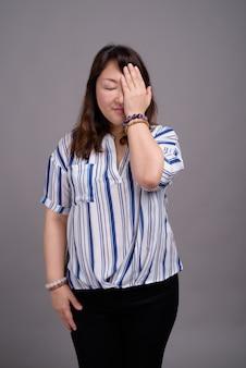 Reife schöne asiatische geschäftsfrau, die gesichtspalme tut
