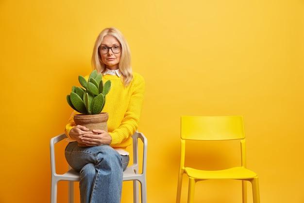 Reife schöne europäische frau hält kaktus im topf kümmert sich um zu hause blumen lebt allein posiert auf bequemen stuhl