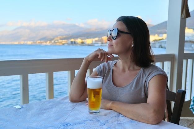 Reife schöne frau, die im seecafé mit kaltem glas bier sitzend ruht