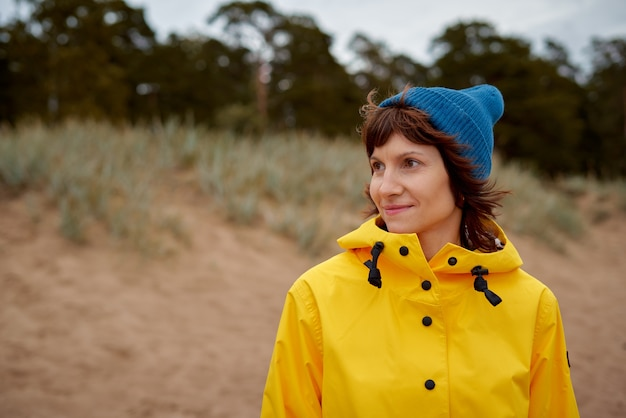 Reife schöne frau, die wald in der leuchtend gelben jacke und im blauen hut sucht
